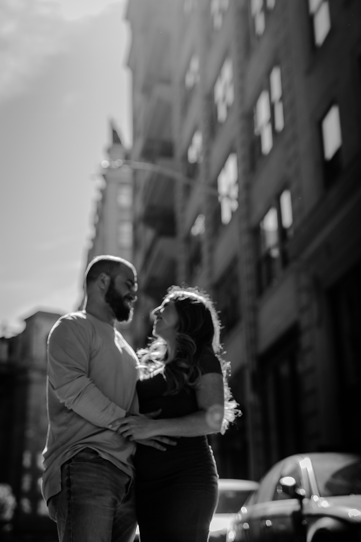 blurred black and white photo of pregnancy husband and wife standing in cobble stoned street in brooklyn during maternity photo shoot. image by krystil mcdowall photography
