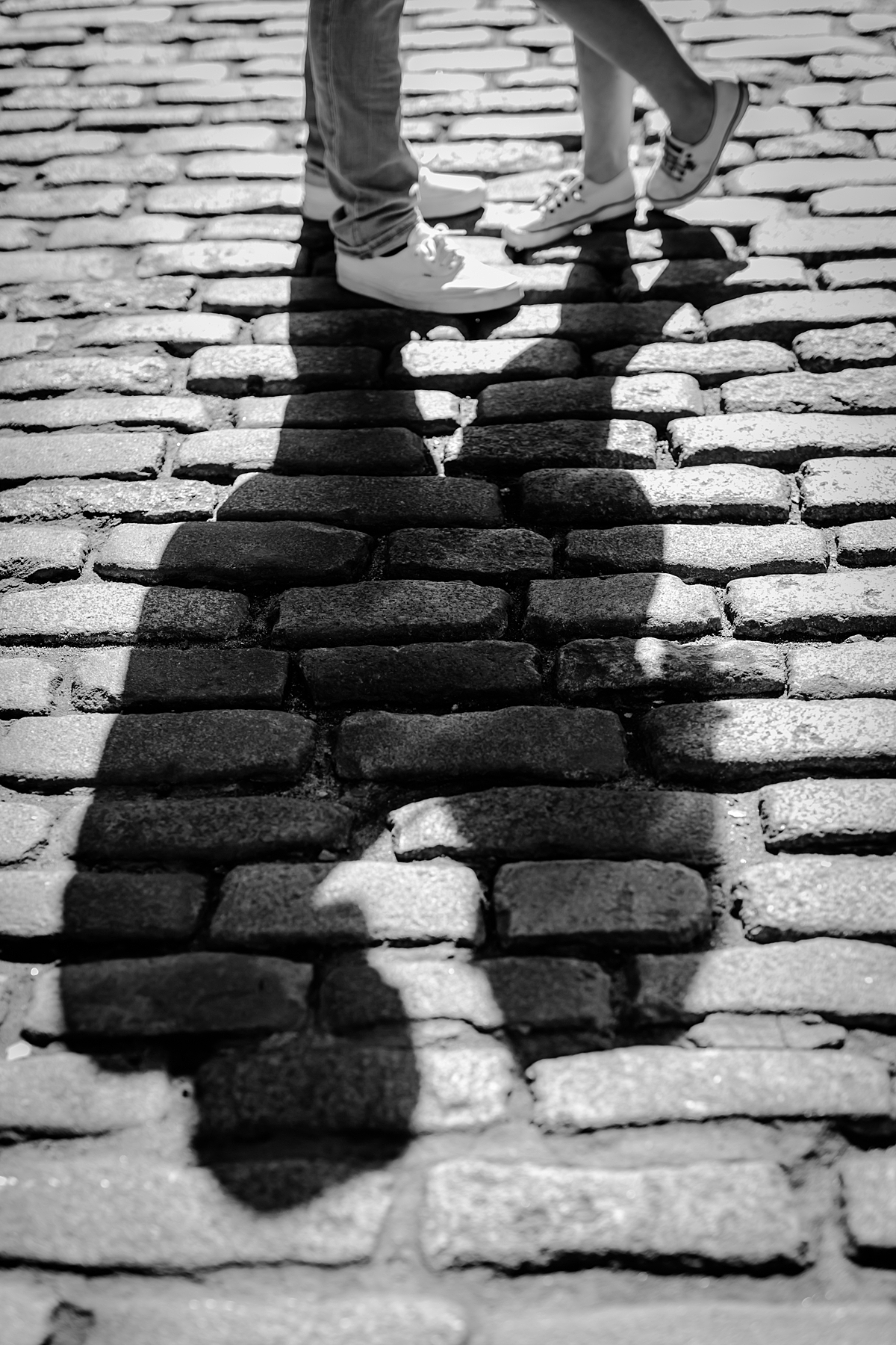 Black and white photo of couple's feet and full body shadow standing on a cobble stoned street during their maternity photo shoot in brooklyn. image by nyc family and newborn photographer krystil mcdowall