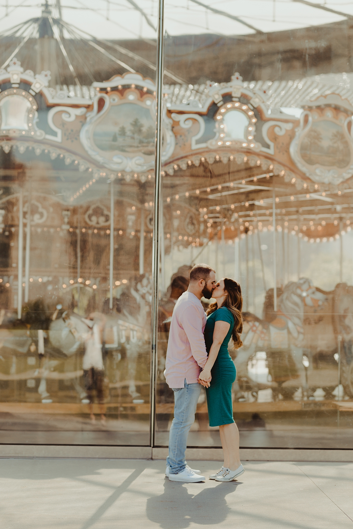 photo of pregnant husband and wife kissing and holding hands in front of jane's carousel during outdoor maternity photo session in brooklyn. image by krystil mcdowall photography