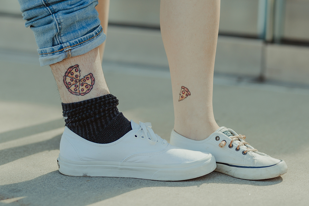 photo of pizza tatoos on legs of pregnant husband and wife taken during outdoor maternity photo session in brooklyn. image by krystil mcdowall photography