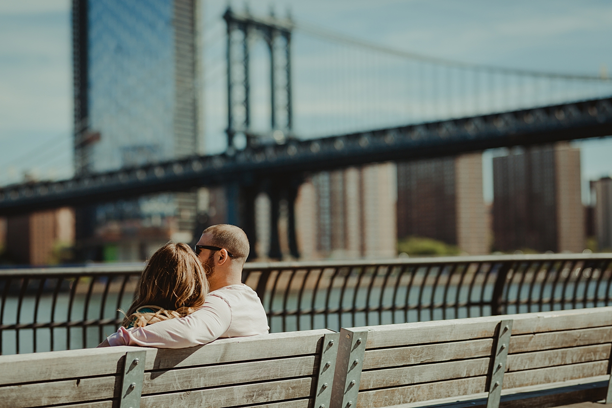photo of pregnant husband and wife sitting on park bench in brooklyn bridge park looking at the manhattan bridge during outdoor maternity photo session in brooklyn. image by krystil mcdowall photography