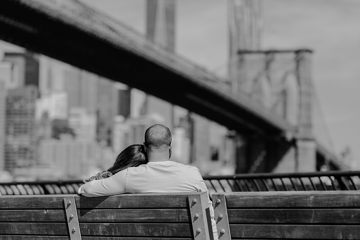 photo of pregnant husband and wife sitting on park bench in brooklyn bridge park looking at the brooklyn bridge during outdoor maternity photo session in brooklyn. image by krystil mcdowall photography