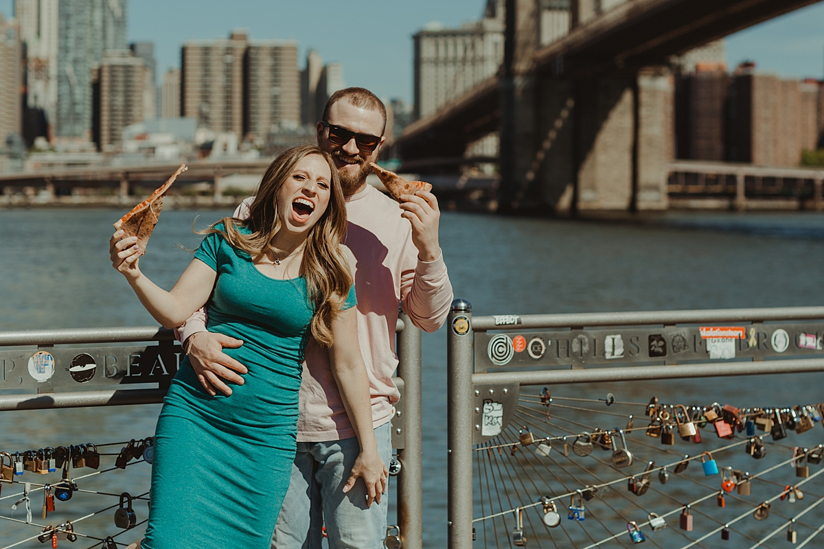 photo of pregnant couple eating pizza in brooklyn bridge park during maternity photo shoot. image by krystil mcdowall photography