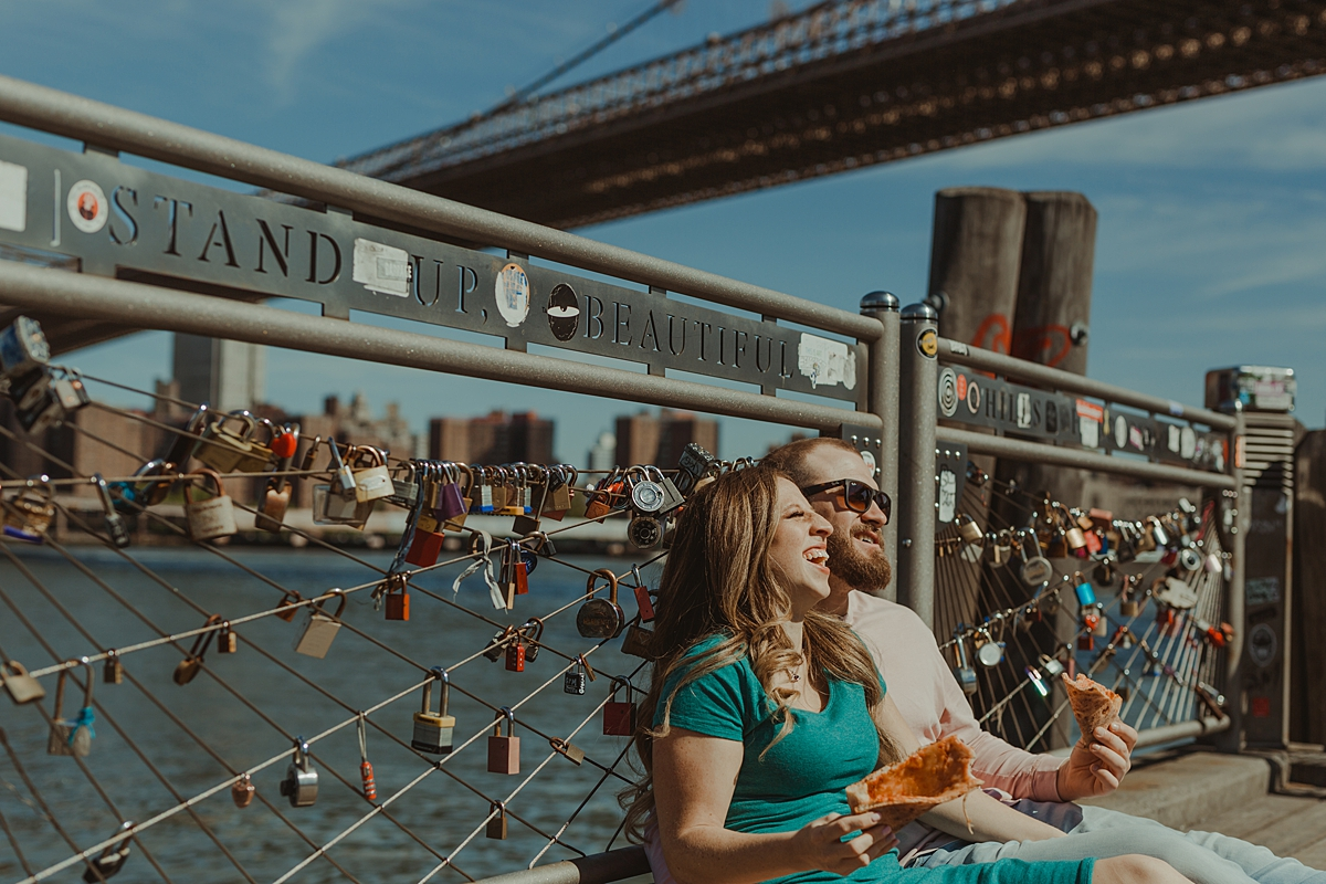 photo of pregnant couple laughing and eating pizza while sitting on the pier at brooklyn bridge park during maternity photo shoot. image by krystil mcdowall photography