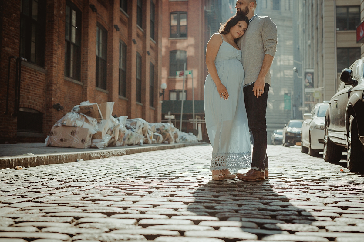 photo of pregnant married couple hugging each other on cobble stoned street during outdoor maternity photo session with orange county family photographer krystil mcdowall photography