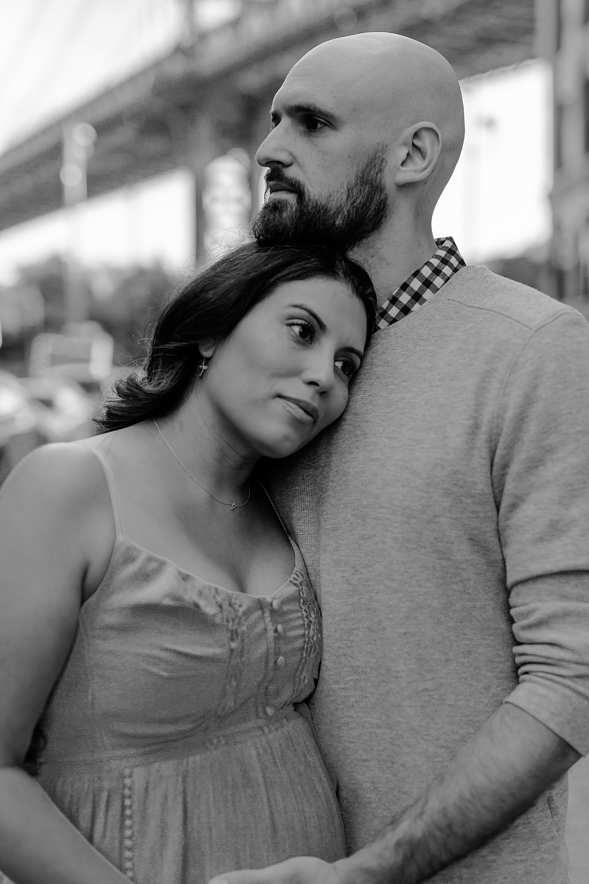close up black and white portrait of married couple standing in the middle of busy city street with bridge in the background while husband touches wife's beautiful pregnant belly during maternity photo session with orange county family photographer krystil mcdowall photography