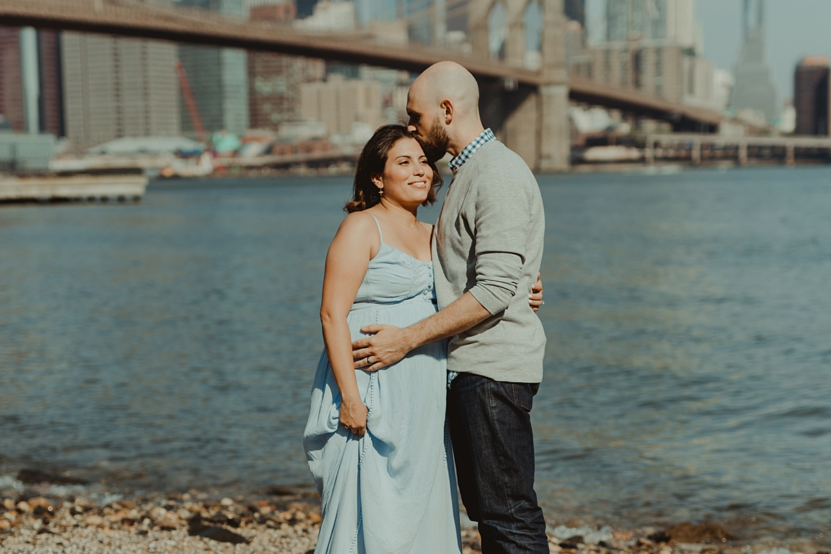 candid moment captured of married couple standing on rocks in front of river with the city in the background for outdoor maternity photo session with orange county family photographer krystil mcdowall photography