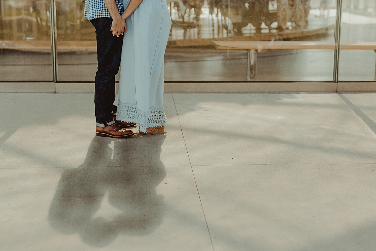 details photo of married couple holding hands in front of children'ts carousel while their dark shadows fall in front of the camera during lifestyle maternity photo session with orange county family photographer krystil mcdowall photography
