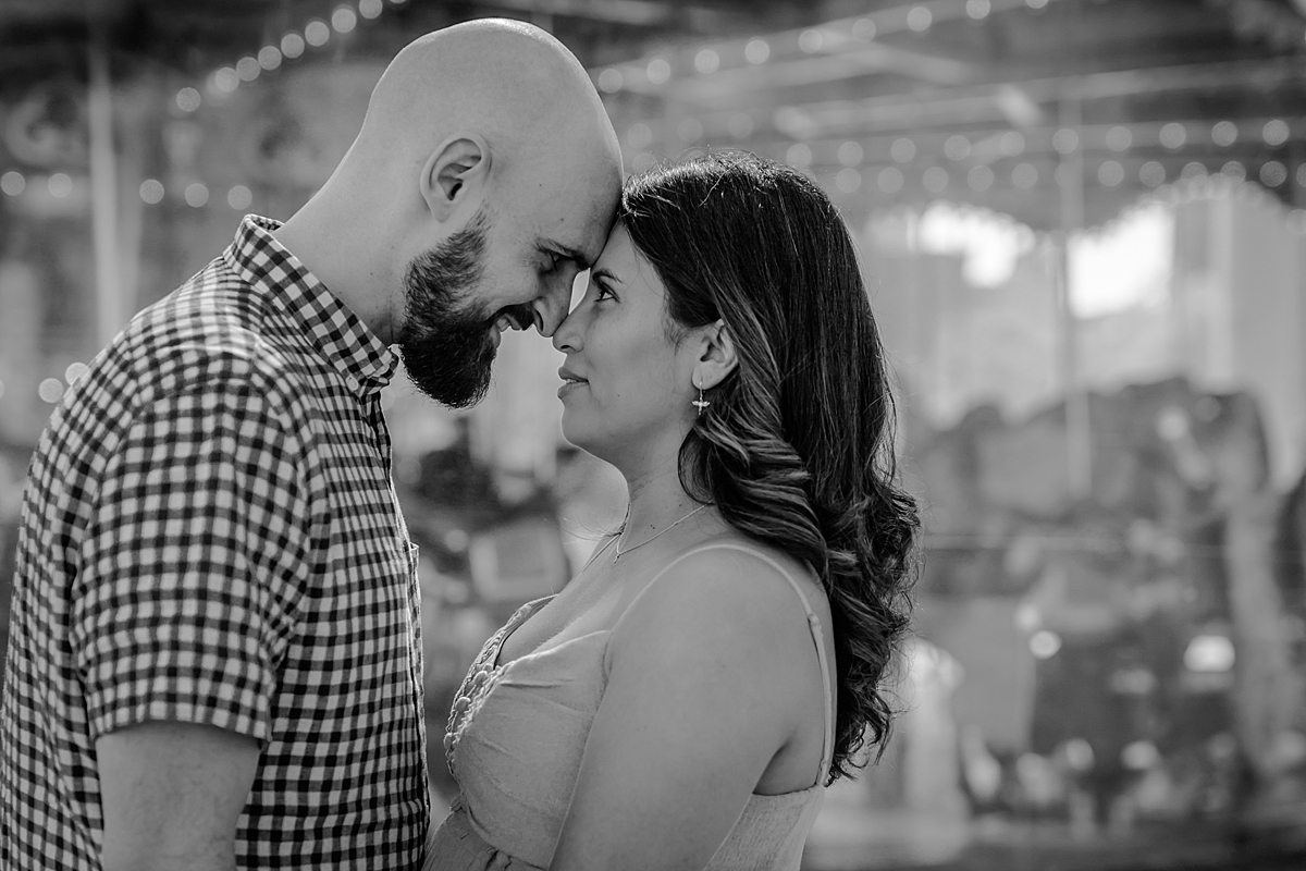 black and white portrait of married couple standing with their foreheads together and looking at each other lovingly during lifestyle maternity photo session with orange county family photographer krystil mcdowall