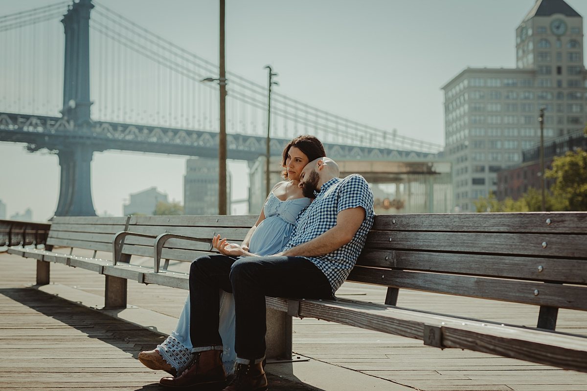 candid portrait of pregnant married couple sitting on park bench together looking out at the river and the city during lifestyle maternity photo session with orange county family photographer krystil mcdowall
