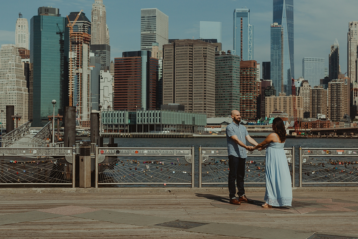 candid photo of pregnant married couple swinging around and being silly on river pier during lifestyle maternity photo session with orange county family photographer krystil mcdowall