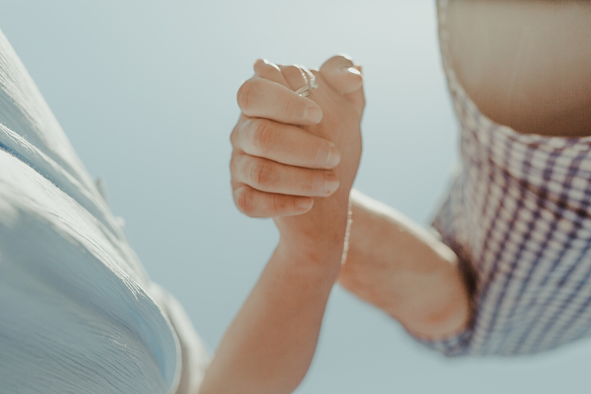 candid image of pregnant married couples hands. image by orange county family photographer krystil mcdowall
