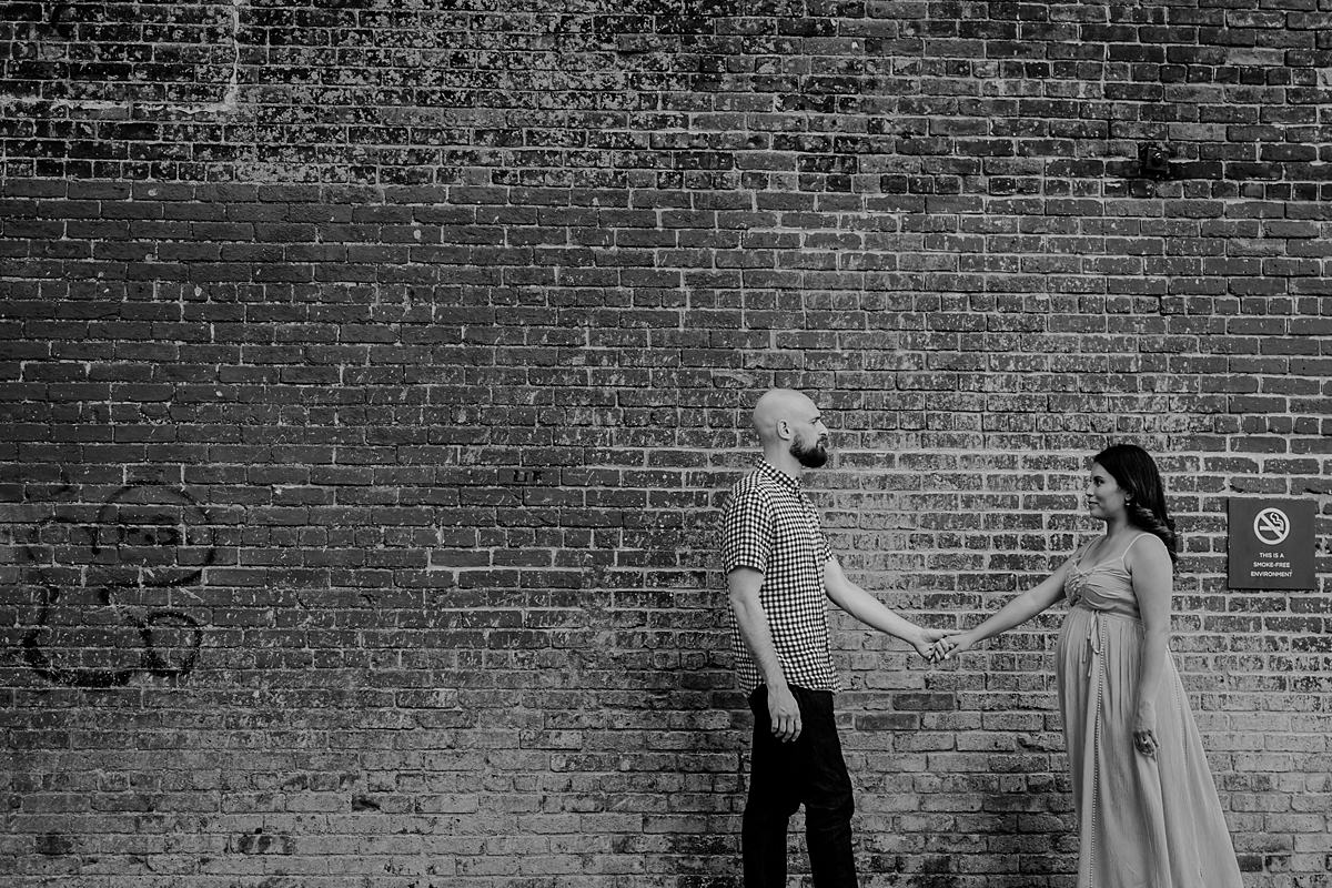 candid image of pregnant married couple walking along the street with brick wall in the background during lifestyle maternity photoshoot. image by orange county family photographer krystil mcdowall