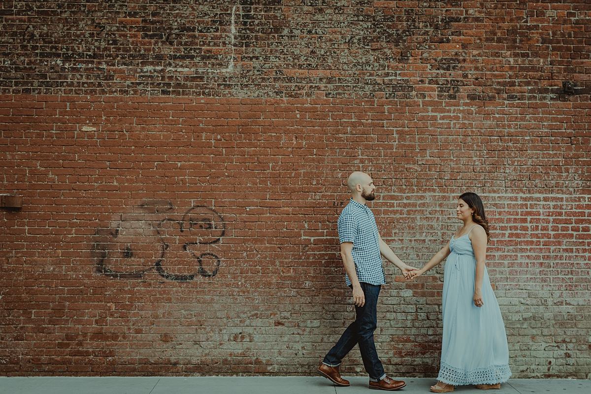 candid image of pregnant married couple walking along the street with gritty brick wall in the background during lifestyle maternity photoshoot. image by orange county family photographer krystil mcdowall