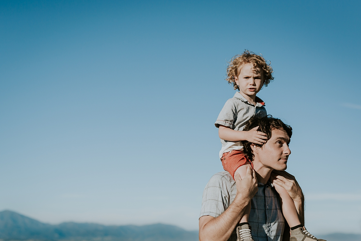 photo by Orange County family photographer Krystil McDowall. Photo of dad giving his cute blonde curly haired son a shoulder ride with mountains in the background during outdoor family lifestyle photo session at Top of the World Laguna Beach California