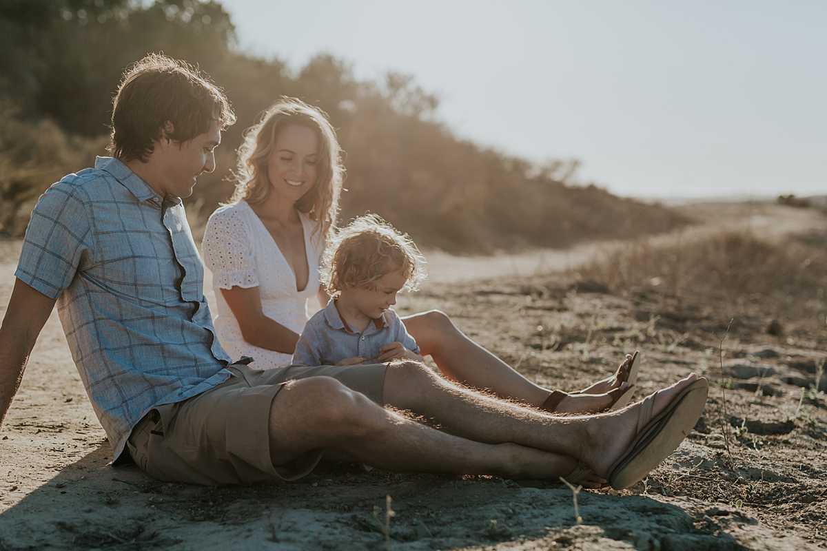 photo by Orange County family photographer Krystil McDowall. Photo of mom, dad and son sitting on the dirt road with son setting in the background during outdoor family lifestyle photo session at Top of the World Laguna Beach California