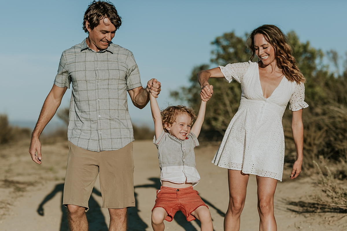 photo by Orange County family photographer Krystil McDowall. Candid photo of dad and mom singing their sweet boy in the air and son standing on dirt road during outdoor family lifestyle photo session at Top of the World Laguna Beach California