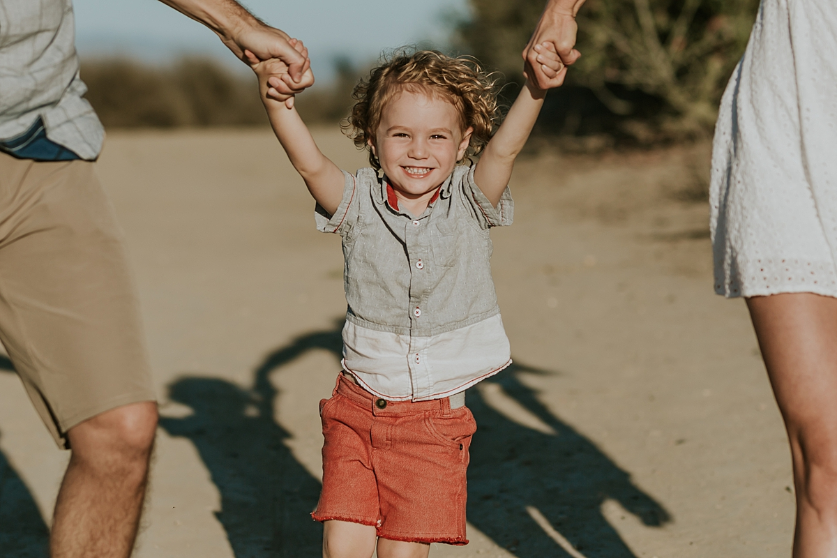 photo by Orange County family photographer Krystil McDowall. Candid toddler boy in red shorts being swung in the air on dirt road during outdoor family lifestyle photo session at Top of the World Laguna Beach California