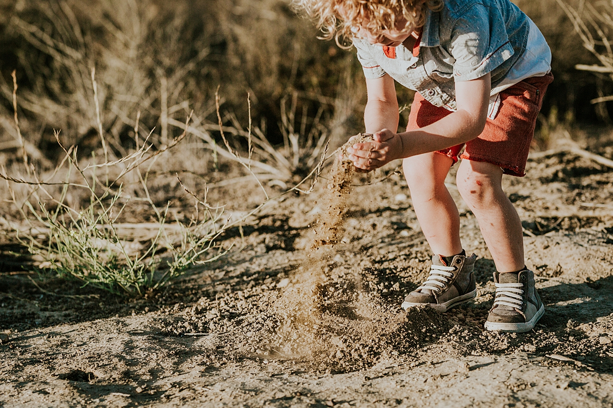 photo by Orange County family photographer Krystil McDowall. Candid photo of beautiful blonde curly haired boy playing with dirt during family lifestyle photo session at Top of the World Laguna Beach California