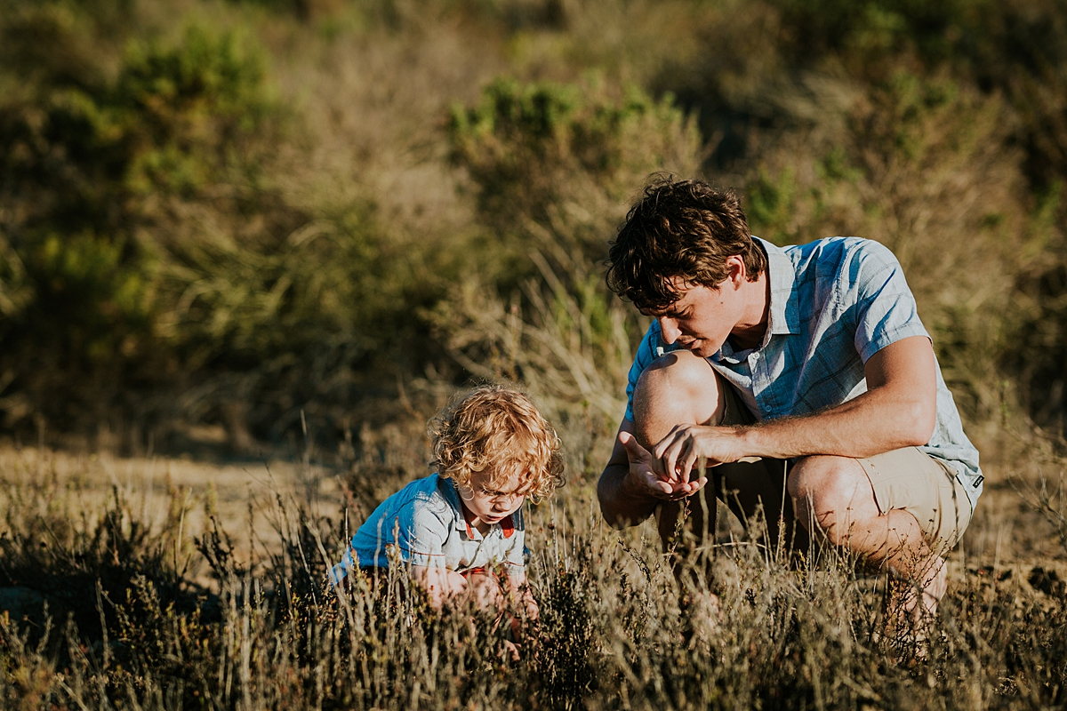 photo by Orange County family photographer Krystil McDowall. Candid photo of dad and son playing in the long grass during family lifestyle photo session at Top of the World Laguna Beach California