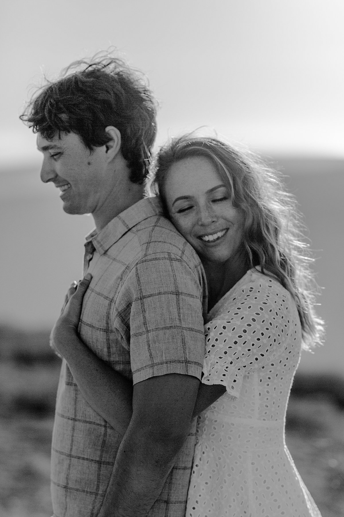 photo by Orange County family photographer Krystil McDowall. Black and white portrait of wife hugging husband and closing her eyes while standing in front of the mountains as the sun sets during family lifestyle photo session at Top of the World Laguna Beach California