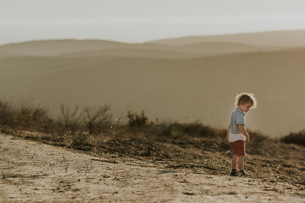 photo by Orange County family photographer Krystil McDowall. Candid photo of sweet boy in red shorts with curly blonde hair exploring the dirt and the mountains as the sun sets during family lifestyle photo session at Top of the World Laguna Beach California