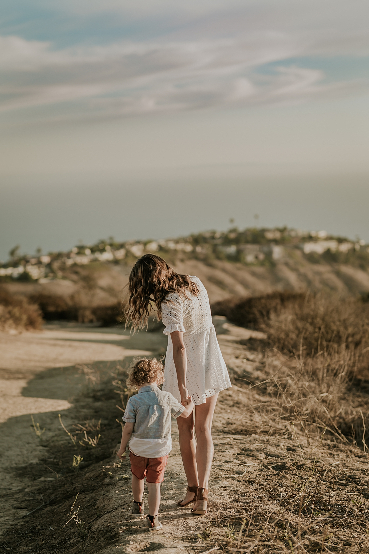 photo by Orange County family photographer Krystil McDowall. Candid photo of sweet boy in red shorts with curly blonde hair holding his mom's hand as they walk along the mountain top during family lifestyle photo session at Top of the World Laguna Beach California