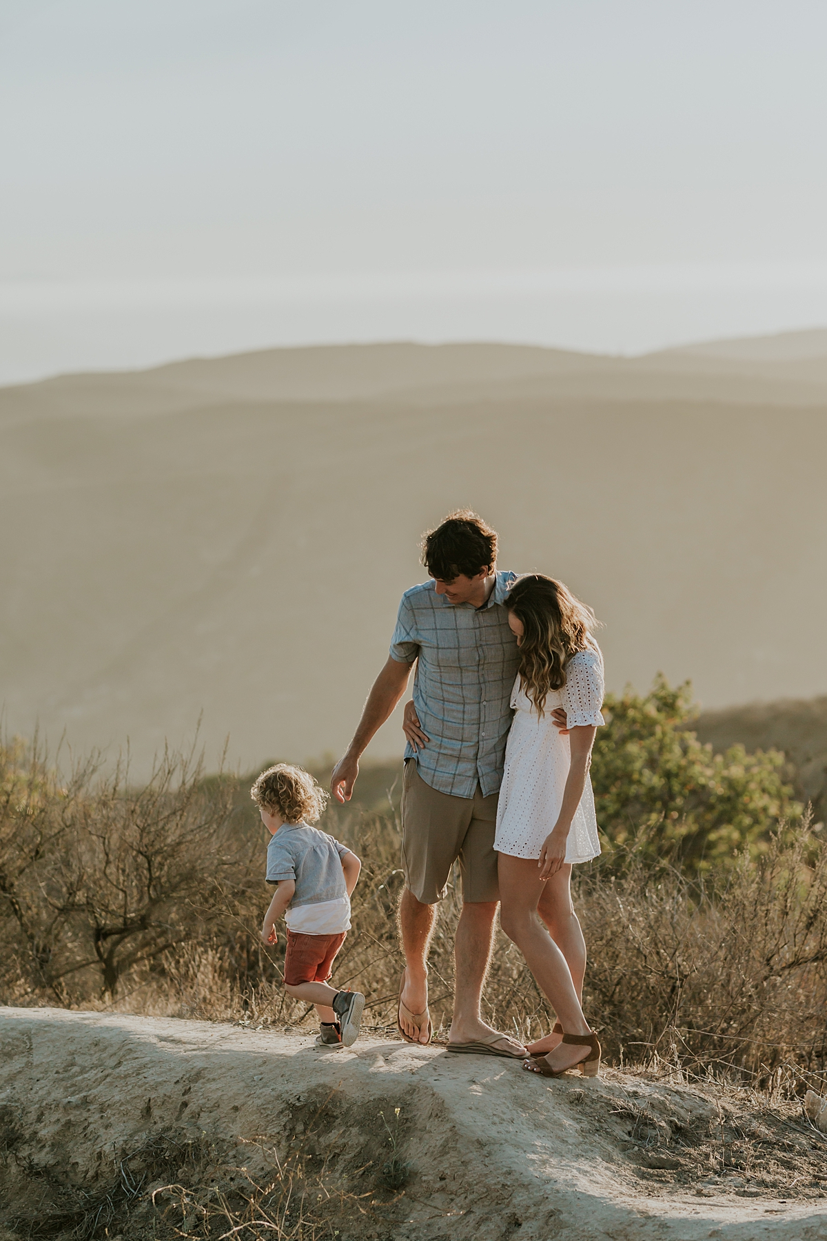photo by Orange County family photographer Krystil McDowall Photography. Photo of mom and dad looking at their son as he runs around the hilltops wduring lifestyle family photo session at Top of the World Laguna Beach California