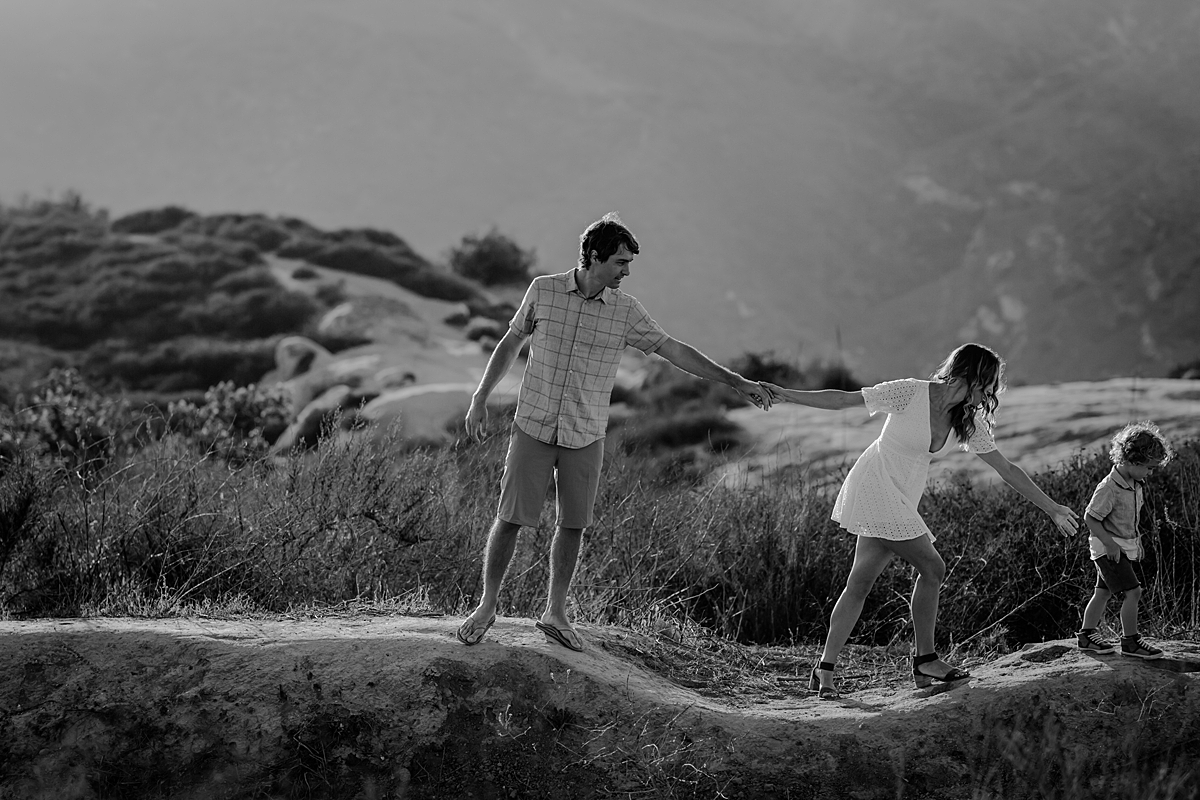 photo by Orange County family photographer Krystil McDowall Photography. black and white photo of mom pulling dad along as they chase their son as he runs around the hilltops during lifestyle family photo session at Top of the World Laguna Beach California