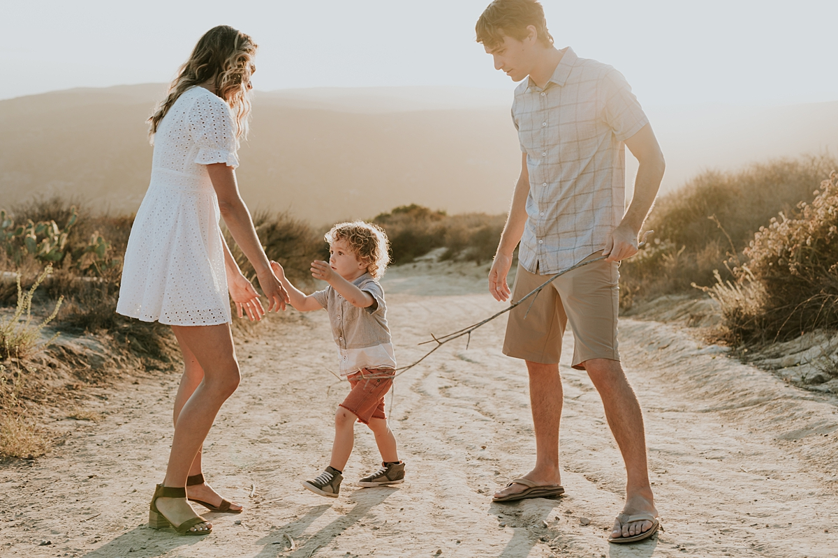 photo by Orange County family photographer Krystil McDowall Photography. photo of son reaching out to mom to pick him up during family photo session at Top of the World Laguna Beach California
