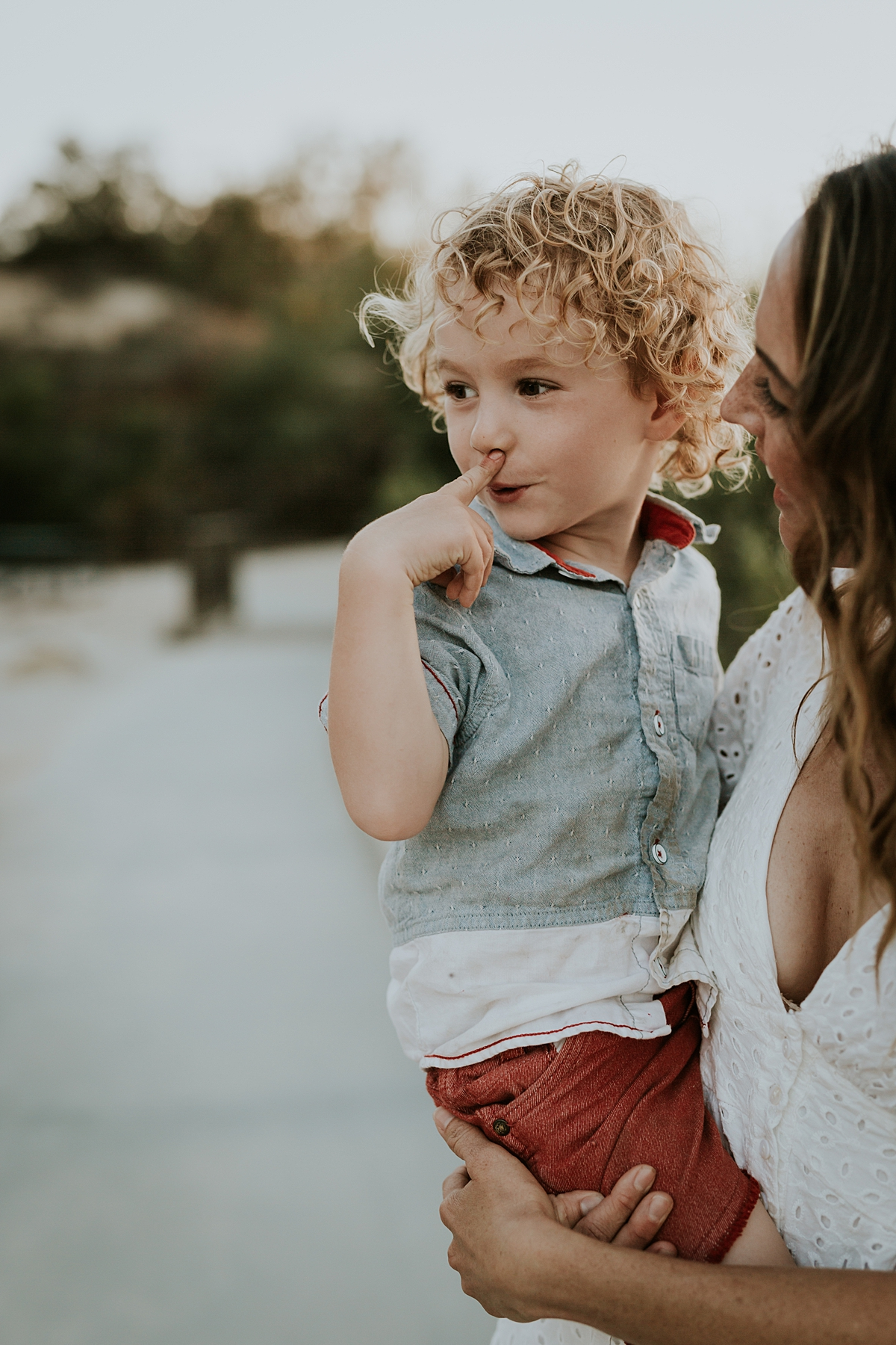 photo by Orange County family photographer Krystil McDowall Photography. photo of mom holding son as he wipes his face during family photo session at Top of the World Laguna Beach California