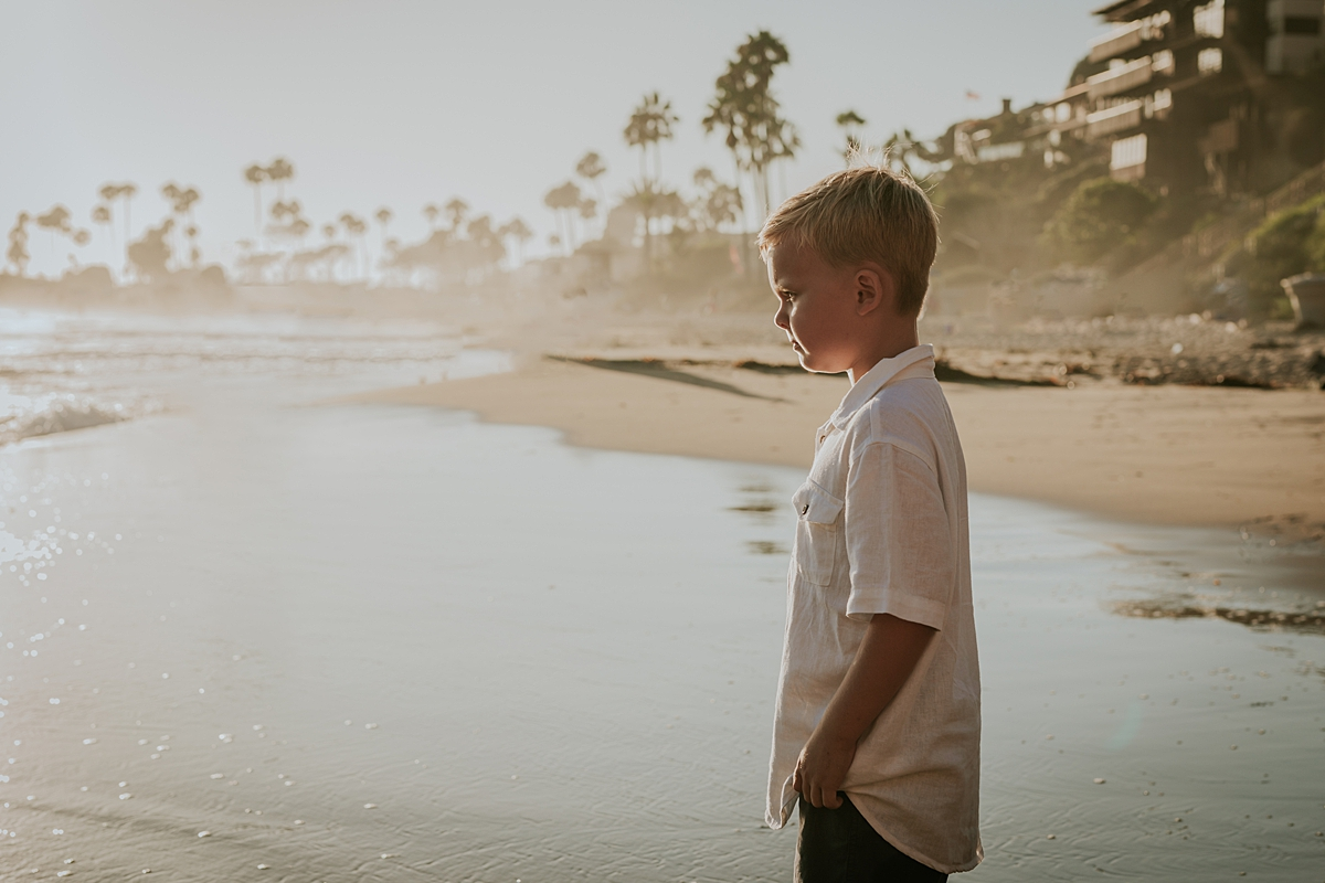 orange county family photographer. photo of boy standing in still ocean water with sun in the background during outdoor family photo session at Corona del Mar State Beach