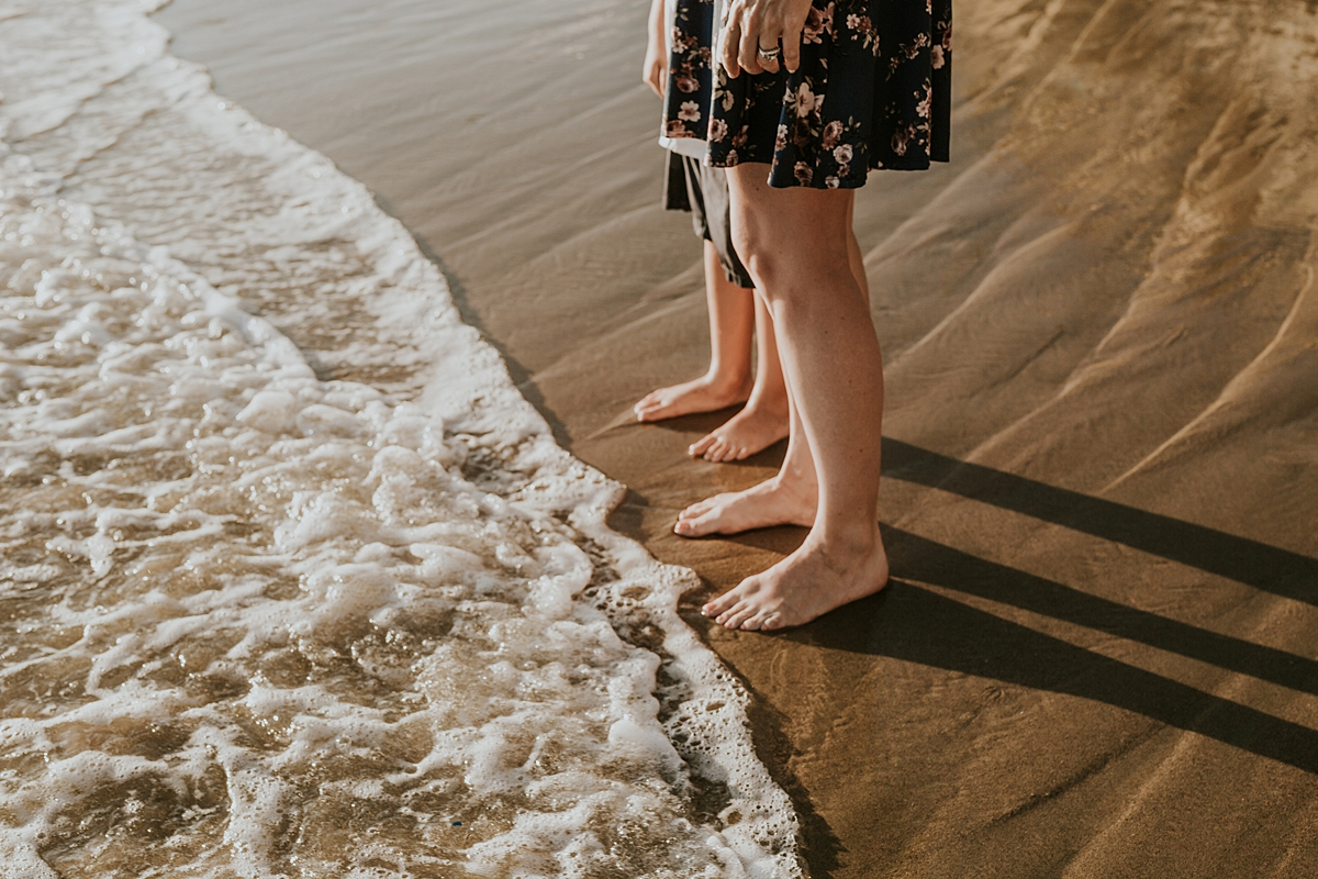 orange county family photographer. photo of mom and son's feet in the sand as the ocean water approached during outdoor family photo session at Corona del Mar State Beach