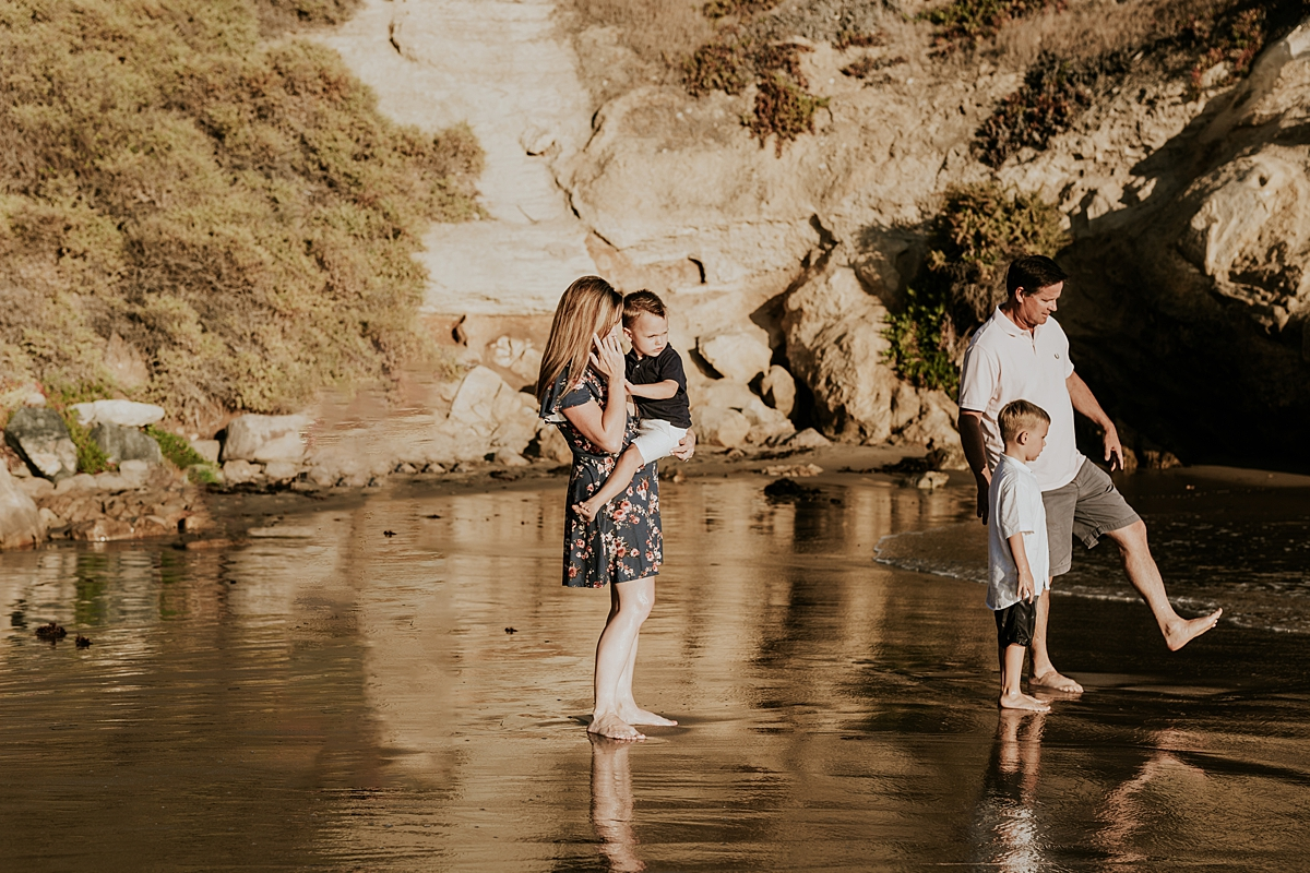 orange county family photographer. family photo of mom, dad and their boys playing in the shallow ocean waves during outdoor family photo session at Corona del Mar State Beach with Krystil McDowall Photography