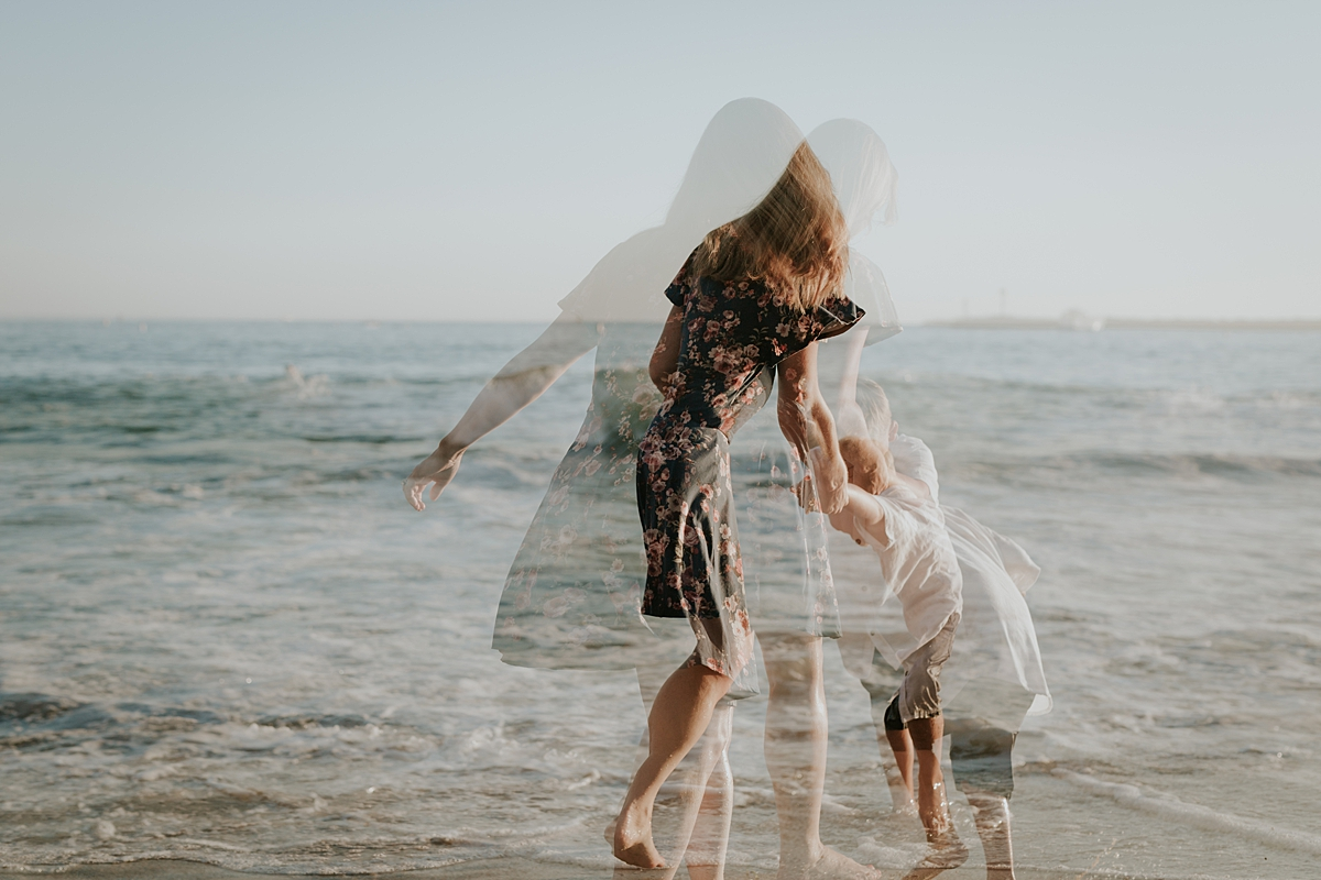 orange county family photographer. double exposure photo of mom and her son running into the ocean waves at Corona del Mar State Beach