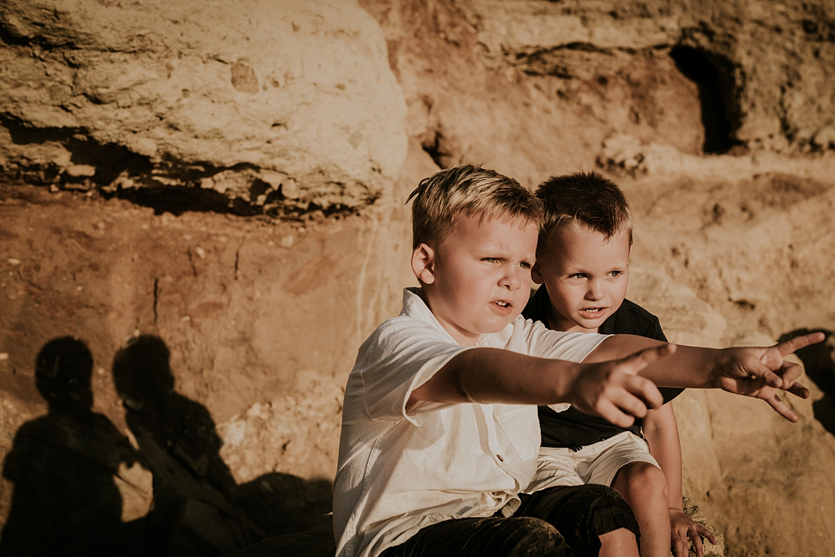 orange county family photographer. candid photo of two brothers sitting on rock bluffs at the beach and laughing and being silly during outdoor family photo session at Corona del Mar State Beach with Krystil McDowall Photography