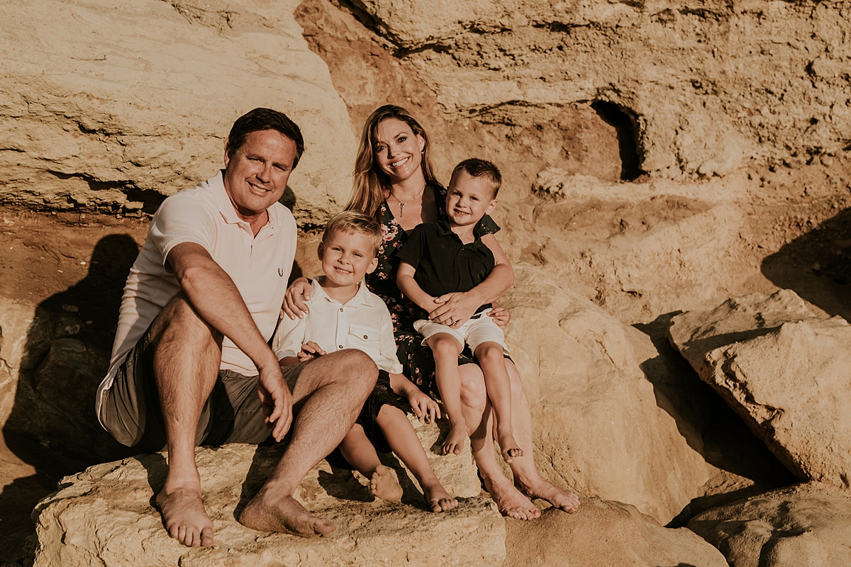 orange county family photographer. photo of family sitting on rock bluffs at the beach during outdoor family photo session at Corona del Mar State Beach with Krystil McDowall Photography
