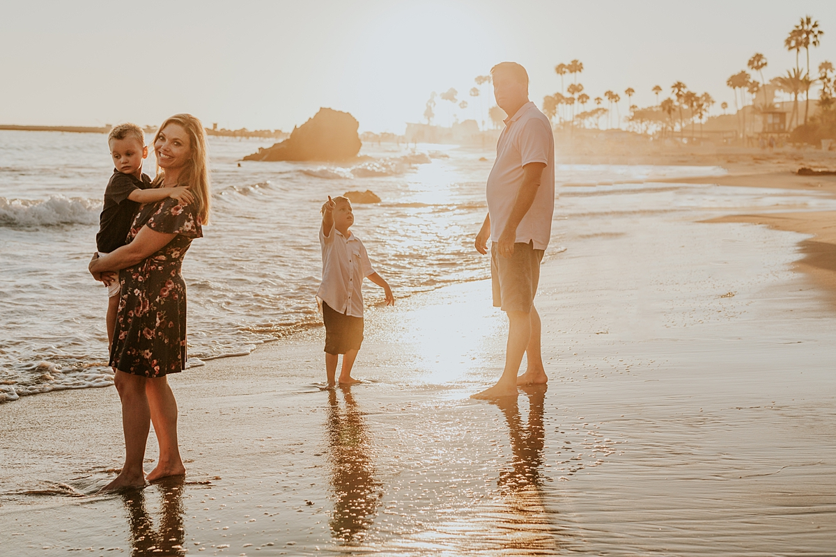 orange county family photographer. candid photo of family as they walk along Corona del Mar State Beach with Krystil McDowall Photography