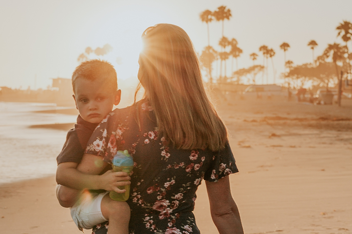 orange county family photographer. photo of mom and son walking along the beach as the sun sets during outdoor family photo session at Corona del Mar State Beach with Krystil McDowall Photography