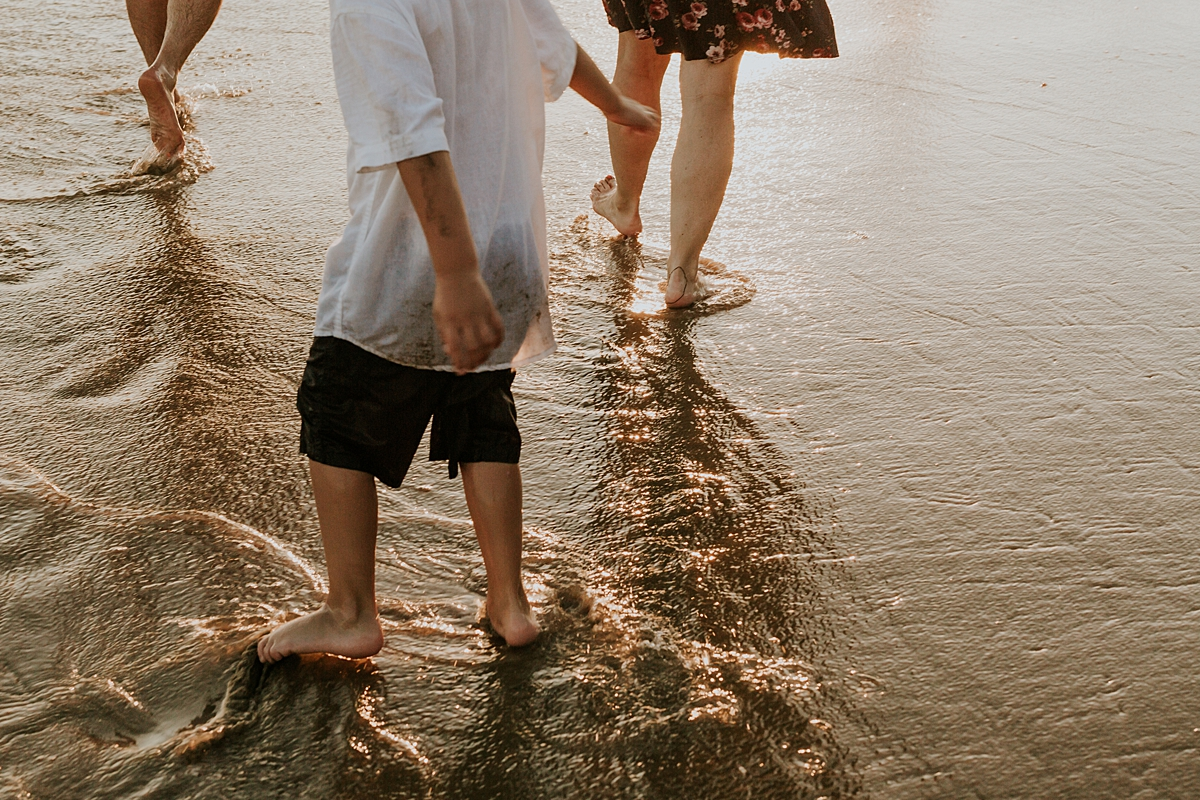 orange county family photographer. photo of feet playing in the ocean water as light from the sun setting hits the water at Corona del Mar State Beach with Krystil McDowall Photography