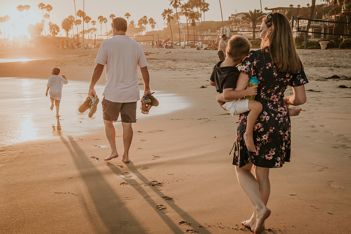 orange county family photographer. candid photo of family as they walk home from Corona del Mar State Beach at the end of family photo session with Krystil McDowall Photography