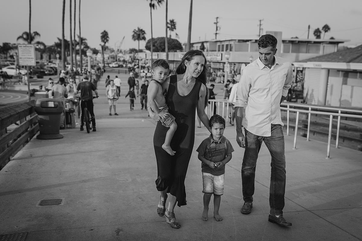 Orange County family photographer. Candid black and white photo of family of four walking along the Huntington Beach Pier during outdoor family photo session with Krystil McDowall Photography