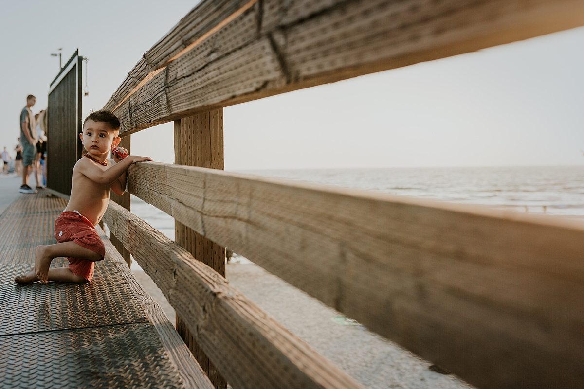 Orange County family photographer. Portrait of young boy in red shorts sitting on the edge of the Huntington Beach Pier during outdoor family photo session with Krystil McDowall Photography