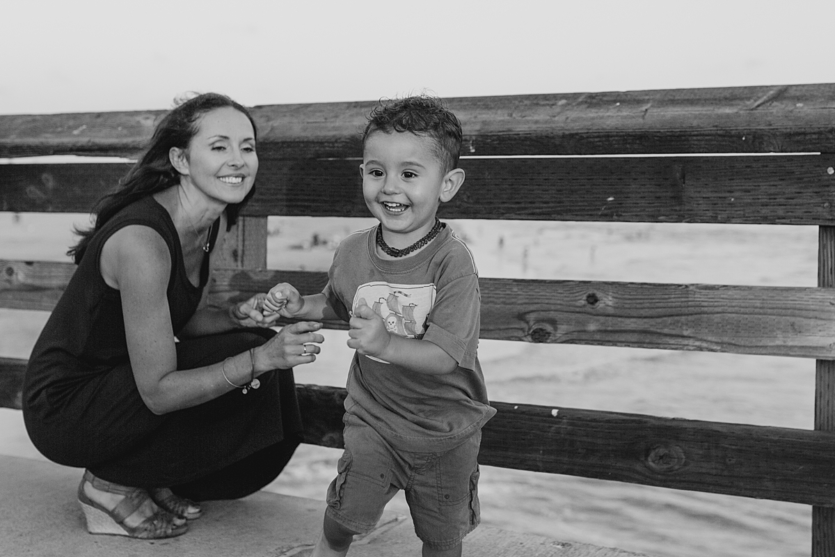 Orange County family photographer. Photo of mom playing with her youngest son as he runs along the Huntington Beach Pier during outdoor family photo session with Krystil McDowall Photography