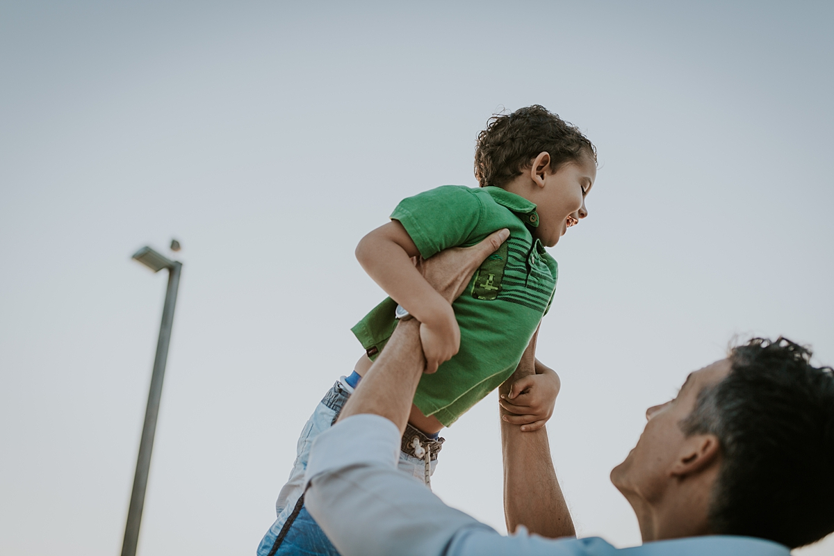 Orange County family photographer. photo of dad throwing oldest son in the air during outdoor family photo session with Krystil McDowall Photography