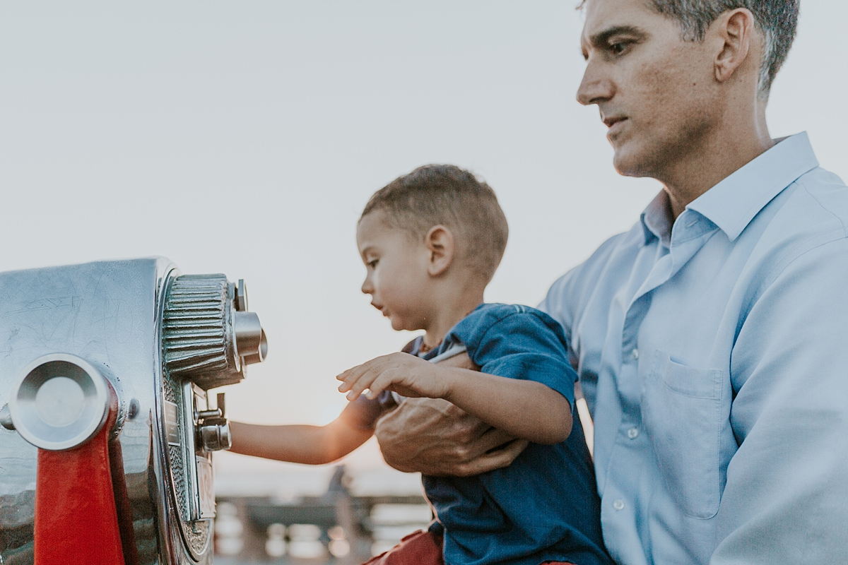 Orange County family photographer. Photo of dad and son playing on the pier at Huntington Beach during family photo shoot with Krystil McDowall Photography