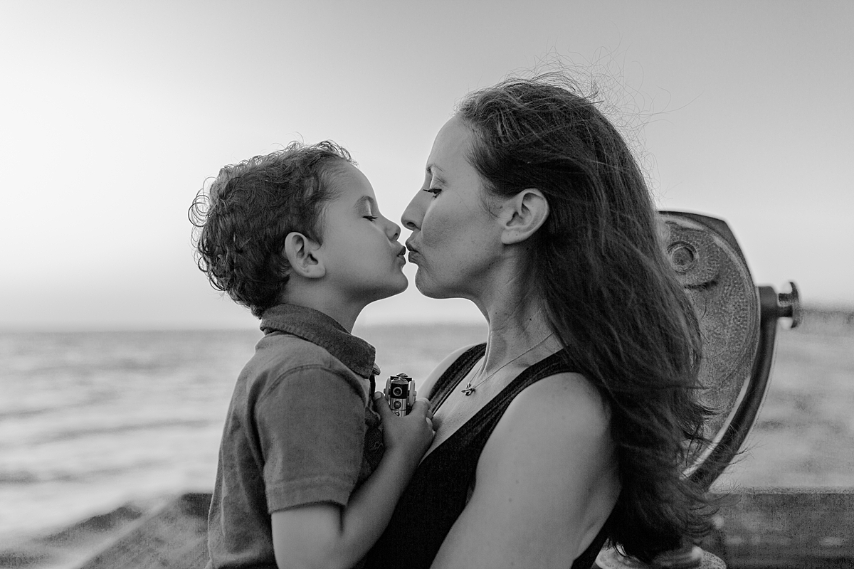 Orange County family photographer. Photo of mom kissing her eldest son on the pier at Huntington Beach during family photo shoot with Krystil McDowall Photography