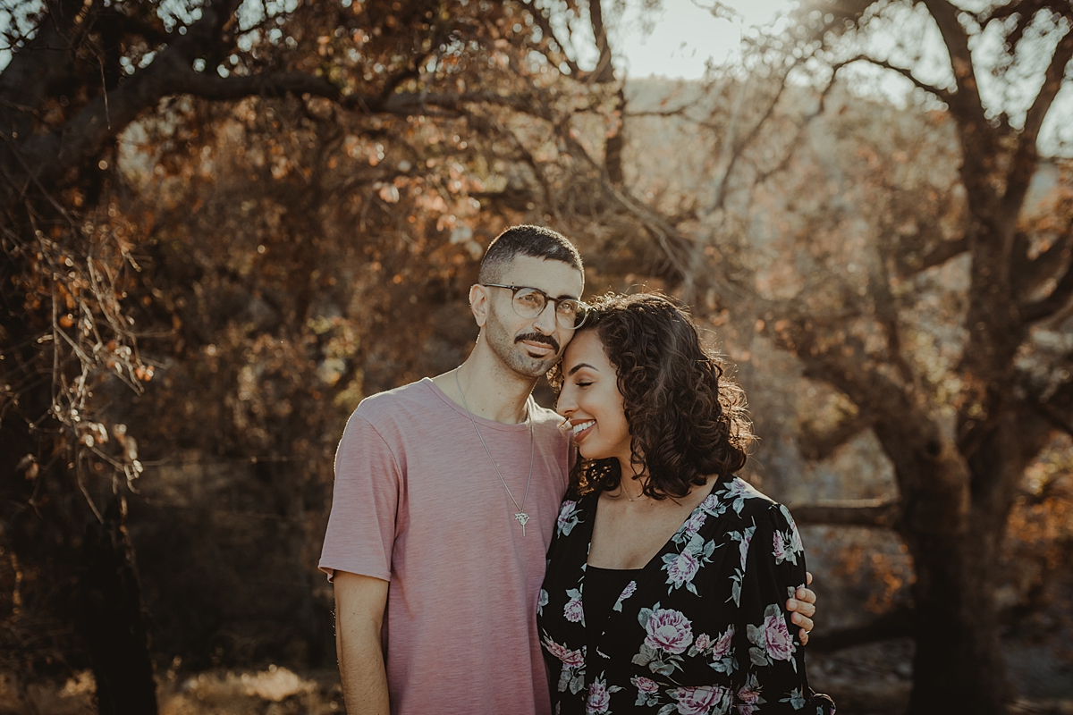 Orange County family photographer. Photo of married couple standing amongst beautiful trees with sun streaming in during outdoor couples photo session in Irvine Regional Park
