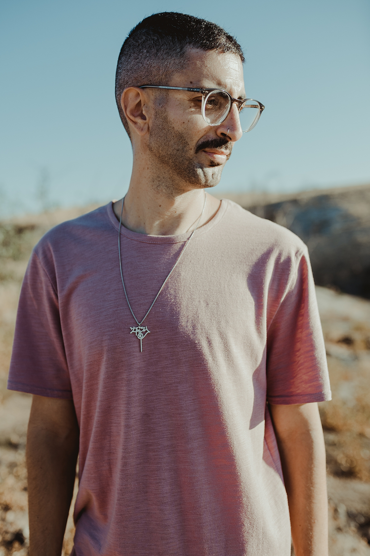Orange County family photographer. portrait of man in pink shirt and silver necklace standing atop the hills at Irvine Regional Park Orange County