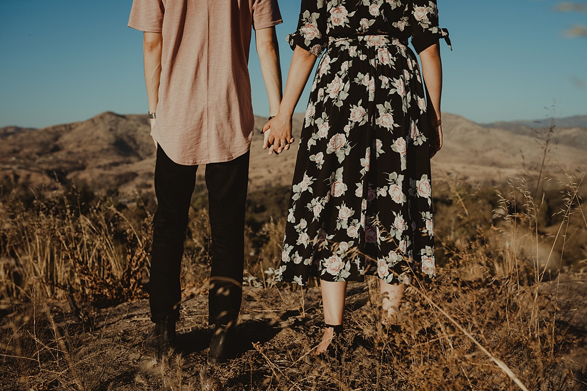 Orange County family photographer. portrait of couple standing atop the hills and holding hands at Irvine Regional Park Orange County